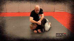 Grabbing the wrist and hand, in the traditional guillotine style grip.