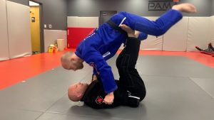 Bring your knees toward your head, lifting him above you, and then over, then coming into the mount position. So, it's a straight over head throw.
