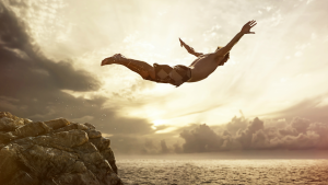 A man jumping into the ocean off a cliff