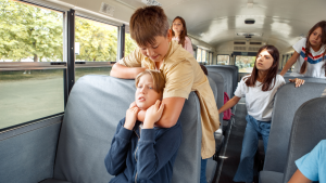 boying choking another boy from behind in the school bus
