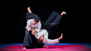 Male martial artist throwing another student