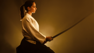 woman holding samurai sword while kneeling