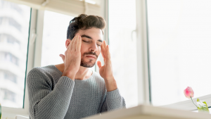 man sitting at a desk stressed closing his eyes and rubbing his head