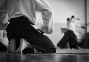aikido student kneeling watching two students practicing