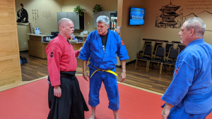 black belt instructor helping students in class