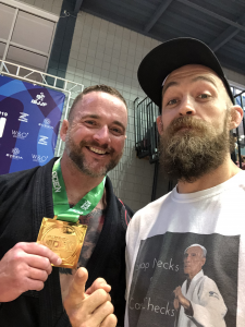 "Josh Olliff and Coach Clay Hantz standing together after Josh won 1st place in the gi division at the IBJJF Dallas Open BJJ tournament. Josh is wearing a black jiu jitsu gi and clay is wearing a white shirt with an old man pictured saying ""Snap Necks. Cash Checks."""